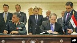 Phó Bộ trưởng Ngoại giao Syria Faisal al-Miqdad (phải) và Phó Cố vấn quân sự về hoạt động gìn giữ hòa bình LHQ Abhijit Guha ký thỏa thuận tại Damascus, ngày 19/4/2012