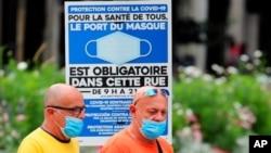 Ljudi nose zaštitne maske prlazeći pored obaveštenja o obaveznom nošenju maski i na ulici, u Bajonu, jugozapadna Francuska, 28. jula 2021.