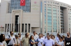 FILE - Journalist are seen gathered outside a court building to support a colleague who was detained in connection with the investigation launched into the recent failed coup attempt in Turkey, in Istanbul, July 27, 2016.