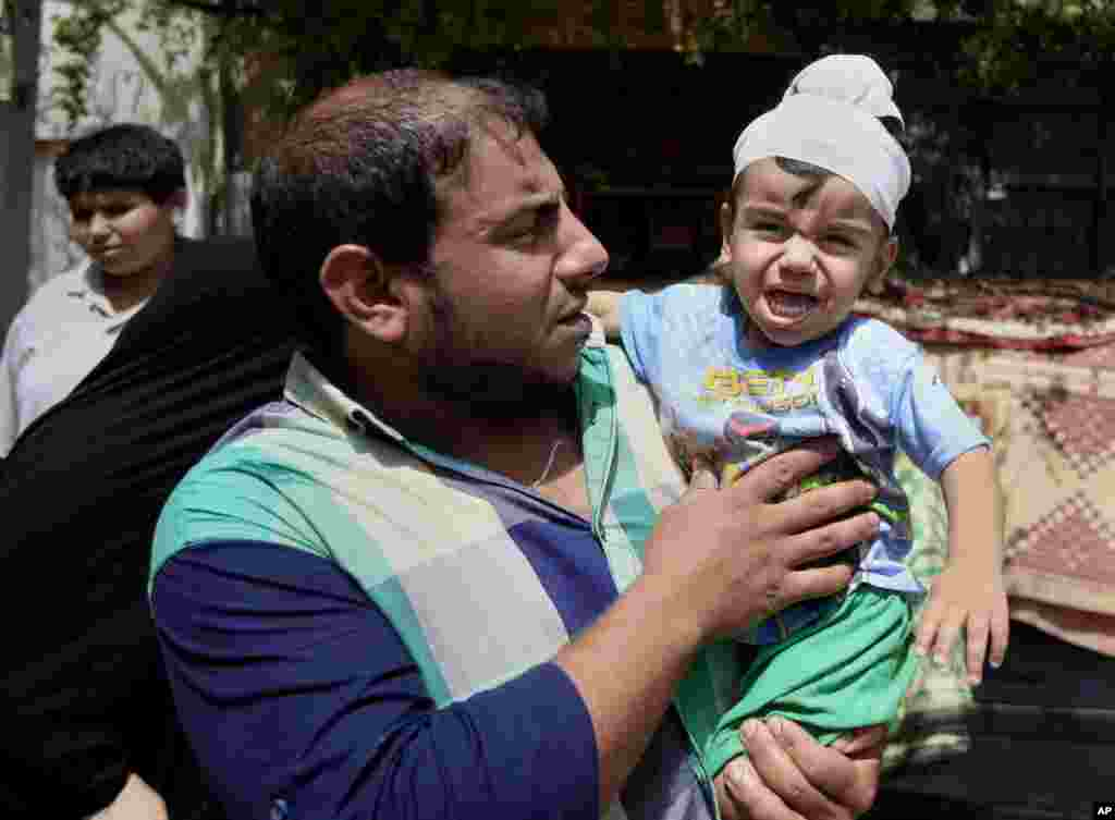 Ali Arar holds his one-year-old wounded son, Aqeel Ali, at the scene of a car bomb attack in the Sadr City neighborhood in Baghdad, May 16, 2013.
