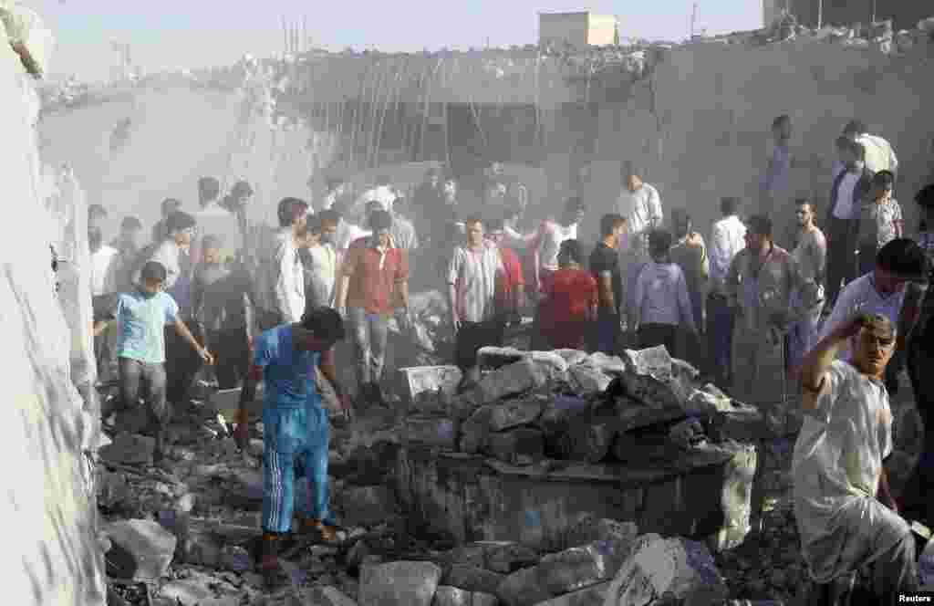 Men search for bodies under rubble of a house destroyed by a Syrian Air force air strike, in Tel Rafat, about 37 kilometers north of Aleppo, Syria, August 8, 2012.
