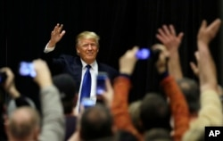 Republican presidential candidate Donald Trump waves to supporters as he arrives at a campaign rally at Clinton Middle School in Clinton, Iowa, Jan. 30, 2016.