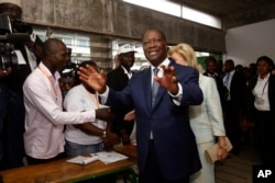 Ivory Coast's president Alassane Ouattara arrives inside a polling station to cast his ballot during elections in Abidjan, Oct. 25, 2015.
