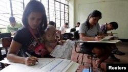 13일 필리핀 마닐라의 한 학교에 설치된 투표소에서 투표용지에 기표하는 유권자들.