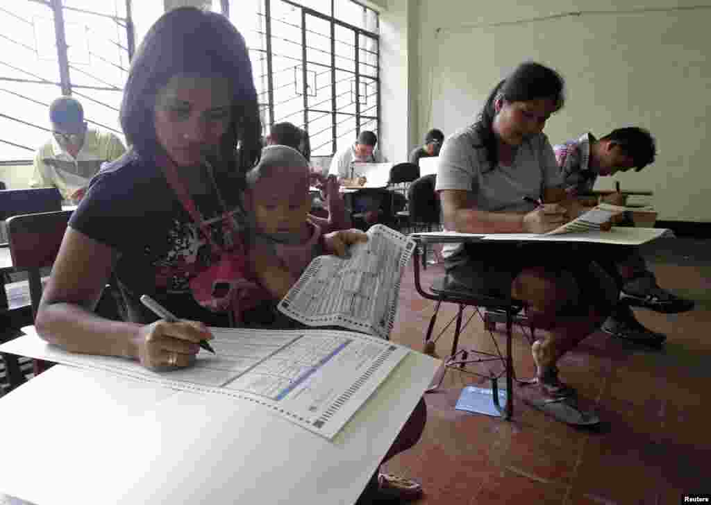 A mother with her daughter fills in a ballot form together with other voters inside a precinct poll at a school in Manila, May 13, 2013.