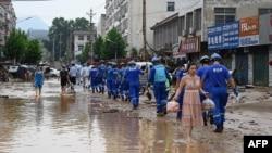 Petugas melakukan pembersihan di Gongyi, dekat Zhengzhou, provinsi Henan, China (22/7).