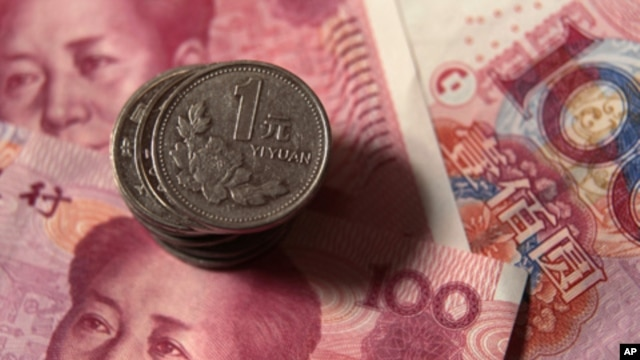 Chinese one-yuan coins placed on 100-yuan banknotes, Dec. 30, 2010 (file photo).