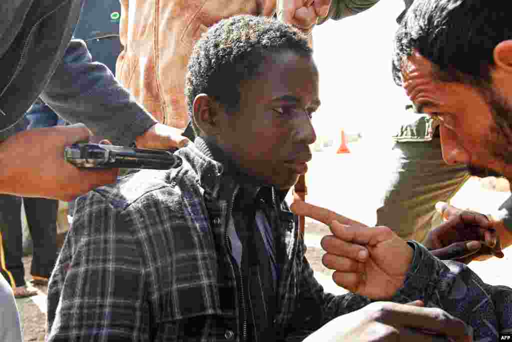 Rebels hold a young man at gunpoint, who they accuse of being a loyalist to Libyan leader Moammar Gadhafi, March 3, 2011. (Reuters)