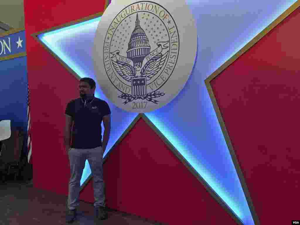 Una persona se toma fotos frente a un símbolo de la Inauguración [Foto: Gesell Tobías, VOA].
