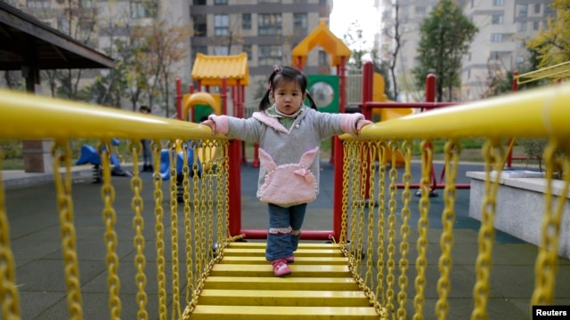 A child walks on a swinging bridge at a kindergarten in Wuhan, Hubei province, December 3, 2012.