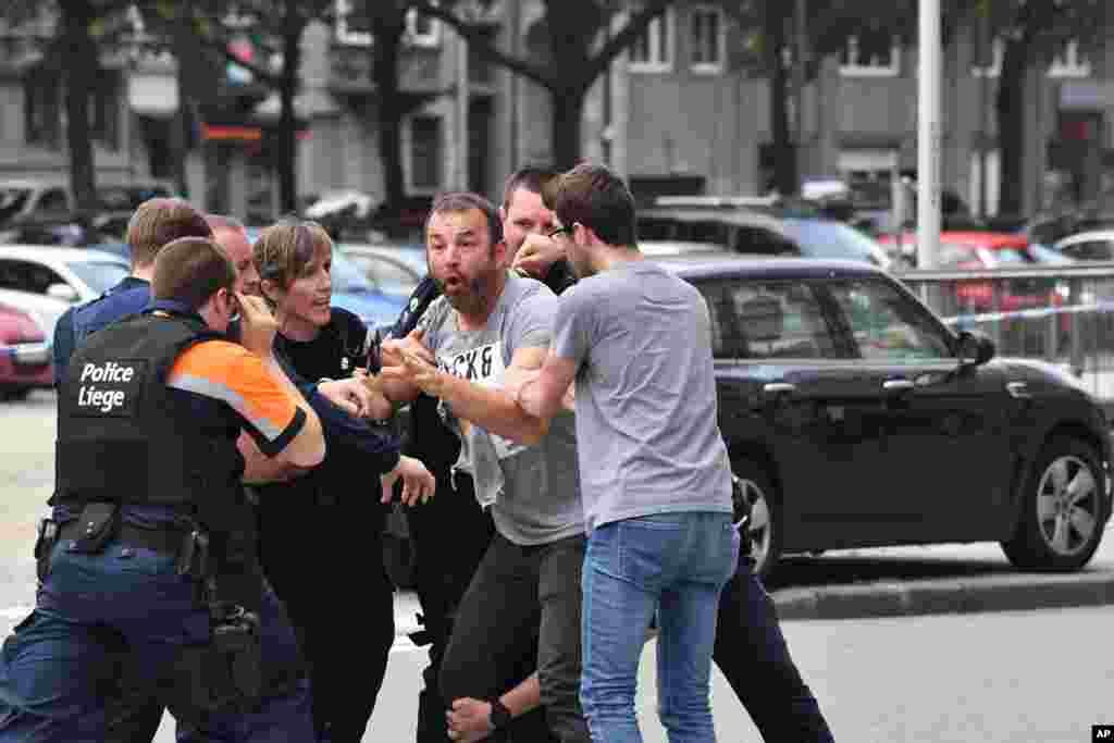 Police try to calm a man at the scene of a shooting in Liege, Belgium. A gunman killed three people, including two police officers in Liege, a city official said. Police later killed the attacker, and other officers were wounded in the shooting.