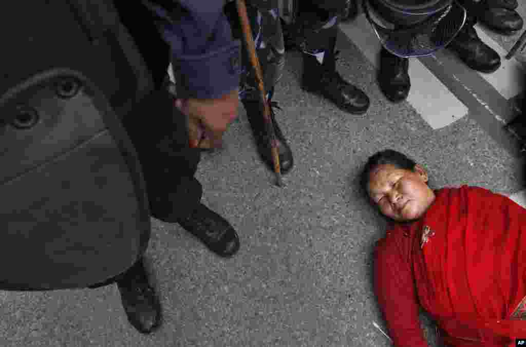 A Nepalese woman lies on the ground during a protest demanding provision in the new constitution to avail citizenship in the name of one's mother, in Kathmandu.