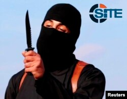 FILE - A masked militant brandishes a knife in this still image from a 2014 video. A new video purportedly shows Islamic State militants beheading three Kurdish peshmerga.
