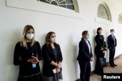 Anggota staf Gedung Putih dan dinas keamana federal Secret Service di lorong West Wing sebelum konferensi pers Presiden Donald Trump mengenai pandemi virus corona, di Gedung Putih, Washington, 11 Mei 2020. (Foto: Reuters)