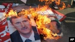 레바논 베이루트 순교자 광장에서 행해진 장례식 도중 바샤르 알아사드 시리아 대통령의 포스터를 불태우는 시민들