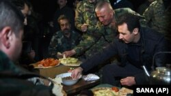 Making a rare visit to the front line, Syrian President Bashar Assad, right, shares a meal with Syrian troops during his visit on the front line in the eastern Damascus district of Jobar, Syria, Dec. 31, 2015.