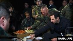 President Suriah Bashar al-Assad (kanan) berbagi makanan dengan tentara Suriah di garis terdepan, saat meninjau mereka di distrik Jobar, Damaskus, Suriah (31/12).