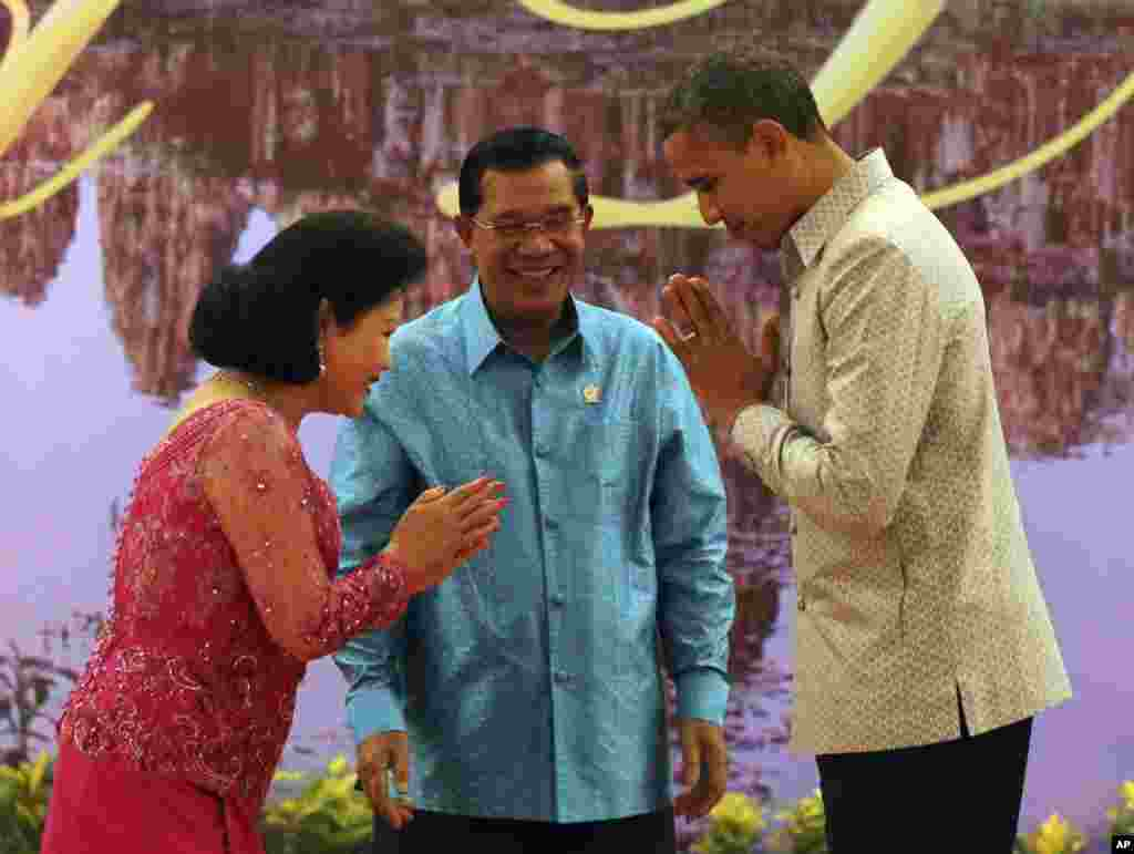US President Barack Obama, right, returns a greeting to Bun Rany, wife of Cambodian Prime Minister Hun Sen, center, prior to a gala dinner in Phnom Penh, Cambodia, November 19, 2012.