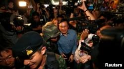 Mantan Menteri Pendidikan Thailand, Chaturon Chaisang (tengah), dikawal ketat oleh tentara dan dikerumuni oleh wartawan seusai memberikan sambutan di Klub Koresponden Asing di Bangkok, Thailand (27/5).