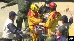 In this image made from video, Lee Tsung-tien, 42, is attended to by rescue workers after he was pulled out conscious from a building which collapsed after an earthquake in Tainan, Taiwan, Monday, Feb. 8, 2016. (AP Photo/APTN)