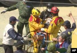 In this image made from video, Lee Tsung-tien, 42, is attended to by rescue workers after he was pulled out conscious from a building which collapsed after an earthquake in Tainan, Taiwan, Feb. 8, 2016.