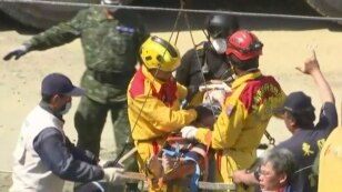 In this image made from video, Lee Tsung-tien, 42, is attended to by rescue workers after he was pulled out conscious from a building which collapsed after an earthquake in Tainan, Taiwan, Monday, Feb. 8, 2016.