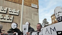 Supporters of WikiLeaks founder Julian Assange, some wearing masks depicting him and holding placards, participate at a demonstration outside the Swedish Embassy in London, 13 Dec 2010