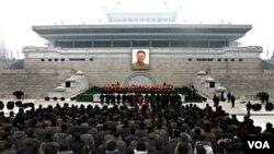 Warga North Korea meletakkan karangan bunga di depan foto besar Kim Jong Il di Pyongyang sebagai penghormatan di tahun baru 2012 bagi mendiang pemimpin mereka (1/1). Foto ini dirilis oleh Sentral Berita Korea dan didistribusikan di Tokyo oleh Kantor Berit