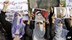 10일 탈레반의 총격으로 중태에 빠진 소녀 마릴라 유사프자이의 사진을 들고 있는 파키스탄 여성들. (자료사진)