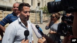 Lebanese father Ali al-Amin speaks to journalists after dropping charges against his estranged wife and an Australian TV crew for attempting to kidnap their children, in front of the courthouse, in the Beirut southeastern suburb of Baabda, Lebanon, Wednes
