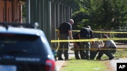 Members of law enforcement investigate an area at Townville Elementary School in Townville, South Carolina, after a shooting, Sept. 28, 2016.