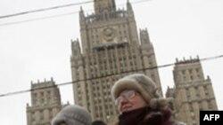 Một người biểu tình cầm cờ của Syria với hình của Tổng thống Syria trong một cuộc biểu tình ủng hộ Syria trước trụ sở Bộ Ngoại giao Nga ở Moscow