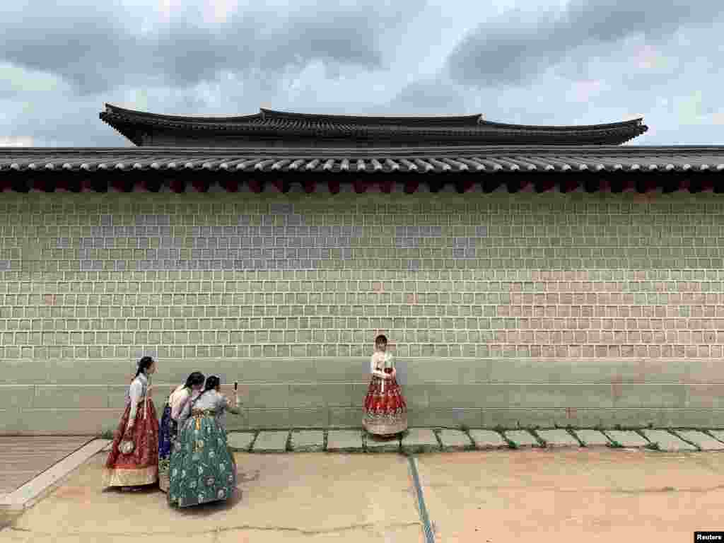 Tourists dressed in traditional Korean costumes take pictures during the visit to Gyeongbokgung Palace in Seoul, South Korea.