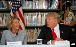 Education Secretary Betsy DeVos listens as President Donald Trump speaks during a round table discussion at Saint Andrew Catholic School, March 3, 2017, in Orlando, Florida.
