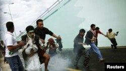 Manifestantes y transeúntes yemenís huyen de la intervención policial que trata de impedir que se tomen la embajada estadounidense en Sanaa.