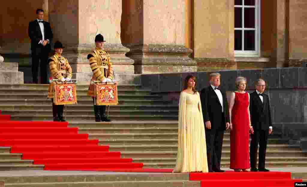 British Prime Minster Theresa May and her husband Philip stand together with U.S. President Donald Trump and first lady Melania Trump at the entrance to Blenheim Palace, where they are attending a dinner with invited guests and business leaders, near Oxford, Britain.