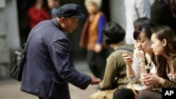 FILE - A beggar asks for money from people sitting at a shopping mall in Shanghai, China, Apr. 19, 2012. Many of China's nouveau riche now are thinking of giving back to society.