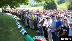 People pray near coffins at a graveyard during a mass funeral in Potocari near Srebrenica, Bosnia and Herzegovina July 11, 2020.