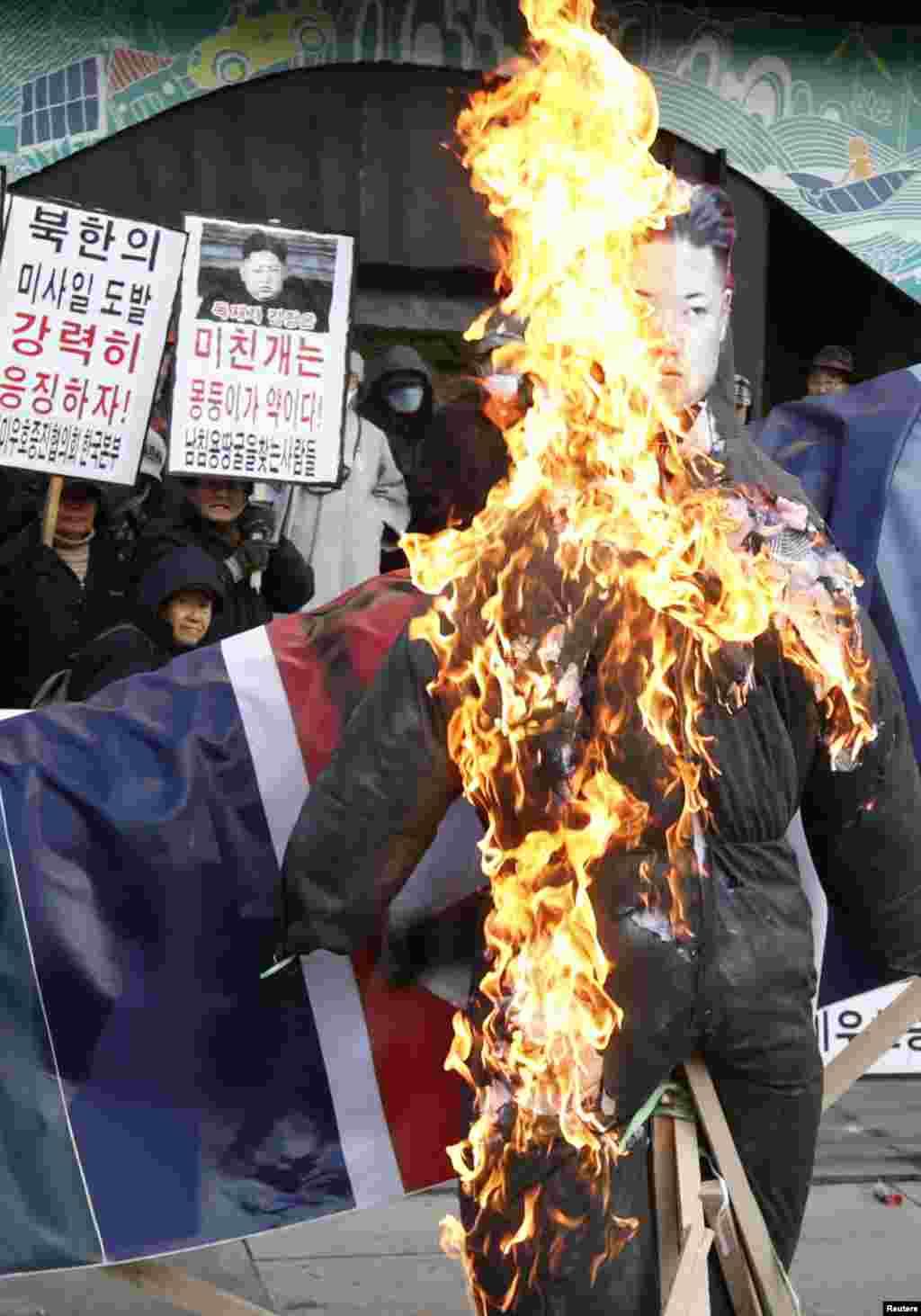 مظاہرین شمالی کوریا کے رہنما کم جانگ کا پتلا نذر آتش کر رہے ہیں