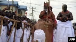 Un collaborateur du palais s'agenouille devant le 40ème monarque du royaume Bénin, Oba Ewuare II, nouvellement couronné sur un pont en bois au cours d'un rite d'intronisation à Bénin City au Nigeria.