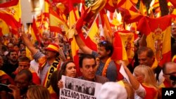 Demonstrators wave Spanish flags as they gather near a headquarters of federal police in Barcelona, Spain, Sunday Oct. 8, 2017. (AP Photo/Francisco Seco)