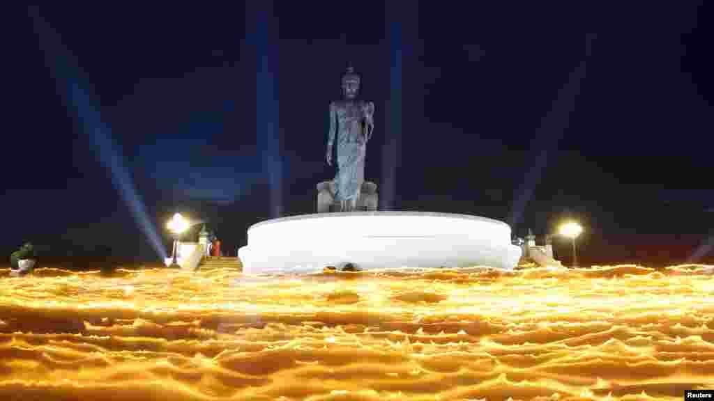 Statua Bude u jednom hramu nedaleko od Bangkoka, uz svjetlo mnogobrojnih svijeća, tokom Vesak dana, odnosno slavlja Budinog rođendana.