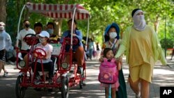 FILE - Chinese families wearing face masks bring their children to a public park during International Children's Day in Beijing, June 1, 2021. China's leaders have announced they will let all couples have three children instead of two, hoping to counter the rapid aging of Chinese society.