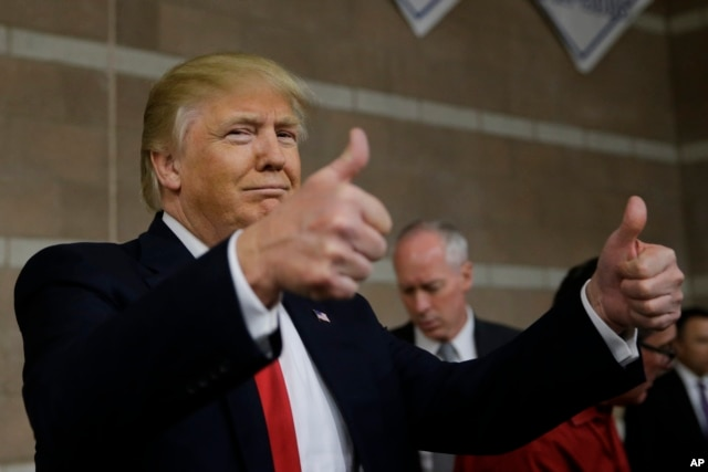 Republican presidential candidate Donald Trump gives thumbs up as he visits a caucus site, Feb. 23, 2016.