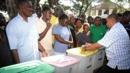 The returning officer for Mvita Constituency, Mombasa,  Gabriel Mwalenga, right, explains to registered voters how the ballot boxes will be used in the forthcoming general elections during an election mock voting exercise.