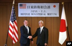U.S. Defense Secretary Ash Carter, left, and Japan's Defense Minister Gen Nakatani shake hands prior to a meeting at the Defense Ministry in Tokyo, Wednesday, April 8, 2015.