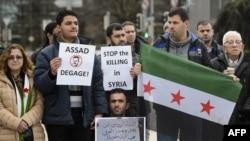 """29일 시리아 평화회담이 열리는 스위스 제네바의 유엔 사무소 앞에서 시위대가 """"시리아에서 살상을 중단하라""""는 푯말을 들고 있다."""