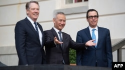 File - US Treasury Secretary Steven Mnuchin (R) and US Trade Representative Robert Lighthizer (L) greet Chinese Vice Premier Liu He (C) as he arrives for trade talks at the Office of the US Trade Representative in Washington, DC, October 10, 2019.