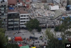 Rescue workers search for people trapped inside a collapsed building in the Roma Norte neighborhood of Mexico City, Sept. 20, 2017.