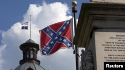FILE - The U.S. flag and South Carolina state flag flies at half staff to honor the nine people killed in the Charleston murders as the confederate battle flag also flies on the grounds of the South Carolina State House in Columbia, S.C., June 20, 2015.